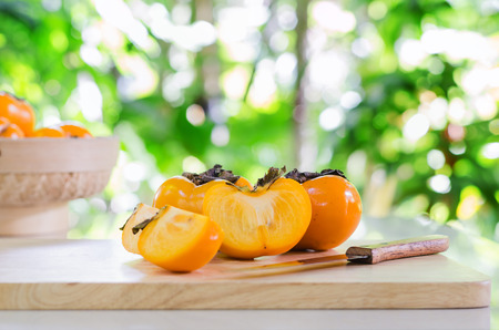 selective focus on yellow persimmon fruits on wood and knife in garden with blur background