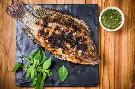 scorch: Grilled fish on black plate prepared with sweet basil and sour-spicy sauce for meal