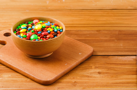 colorful button-shaped chocolate in wood bowl on wood table Stock Photo