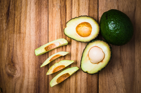 cut and sliced avocados on wood table, an exotic fruit or vegetable is growth in spring, scientific name is persea
