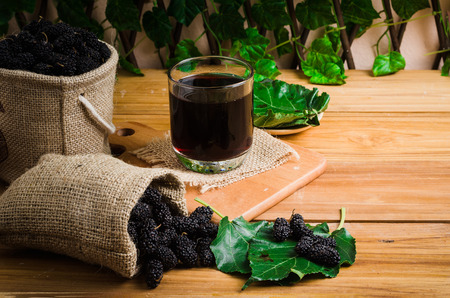 glass of mulberry juice be side by mulberry sackcloth on wood table and leaf, healthy-fruit drinking, raspberry or blackberry
