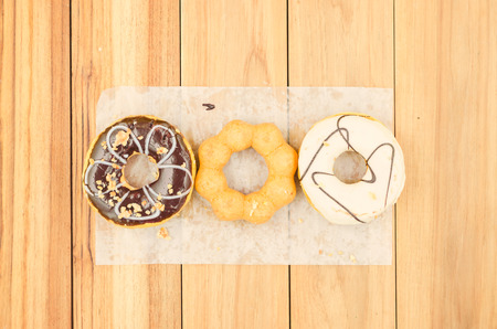 alignment of doughnuts on wood table. A dessert made with deep-fried of a flour dough.
