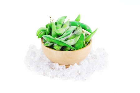 Frozen edamame or soybean surround with ice on white with clipping path, it is a cuisine of Japan, China and Asian