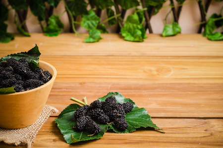 Mulberry, raspberry or blackberry put in bowl and leaf on wood table and copy space Stock Photo