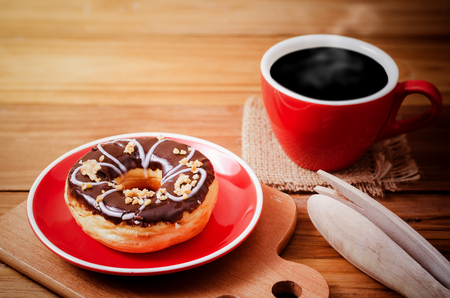 doughnut and red cup of coffee with warm light in the morning. feeling freshness after breakfast
