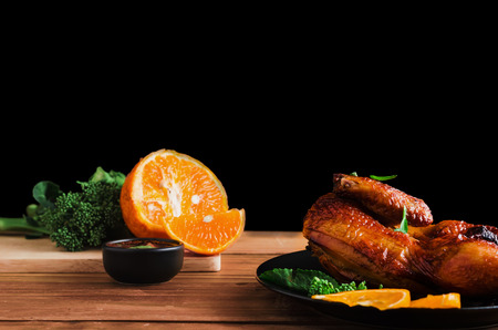 chicken grilled on plate with black background and wood table prepared with spicy dipping, orange fruit and vegetable