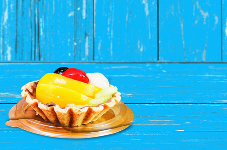 selective focus at fruit tart to blured background, a dessert prepared with mixed fruit put on blue wood table