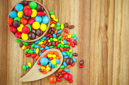 colorful button shape candy made from chocolate covered with color put on wood has space for some text