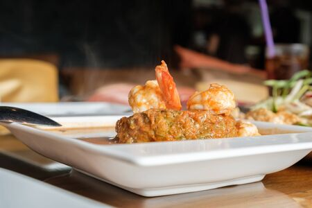 selective focus at shrimp of Thai foods acacia omelets and fresh shrimp in vegetable sour soup in white bowl on table Stock Photo