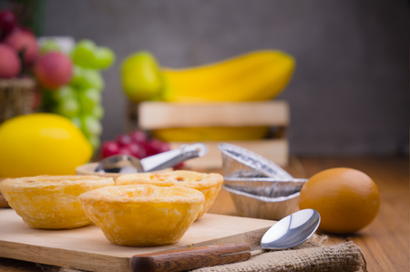 selective focus on tart bakery put wooden with spoon , egg and used foil cup decorate with some fruit in still life style