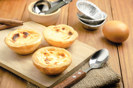 horizontal view of egg tarts put on the wood table with spoon