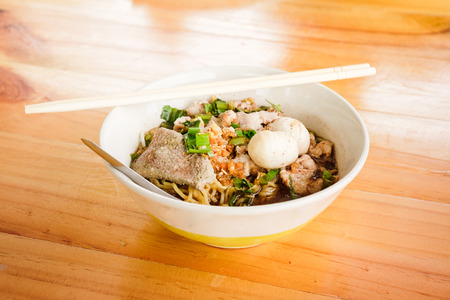 bowl of noodle, cooking with pork liver, meat, and balls, having spoon and chopsticks put over the bowl