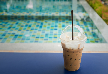 iced coffee with swimming pool background and copy space for any text