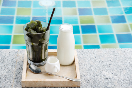 glass of iced milk greentea and bottle of milk put on tray near swimming pool background