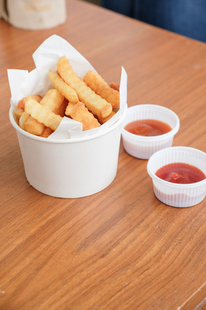 selective focus on French fries cup on wood table wtih chili sauce and tomato sauce Stock Photo