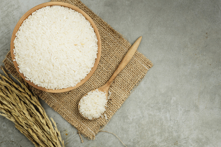 top view of rice in wooden bowl on concrete texture with copy space