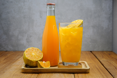 the bottle of orange juice and a glass of orange juice put on wood table with negative space