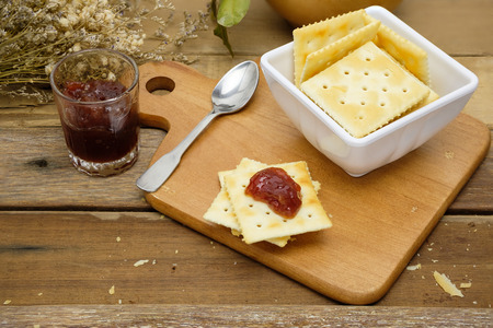 delicious saltine crackers spread with strawberry jam beside with a cup of crackers and glass of strawberry jam as well as spoon Stock Photo
