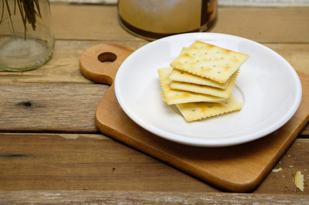 saltine crackers on white plate put on wood table with copy space for any text Stock Photo