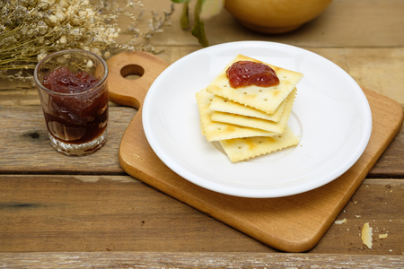 delicious crackers topping with strawberry jam in white dish on wood table with copy space for any text