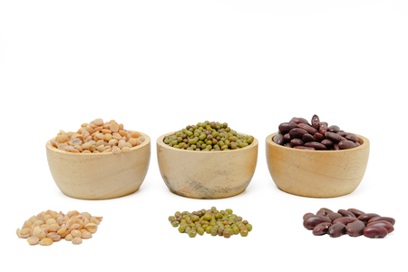 kind of beans in wooden cup are aligned on white background with clipping path, there are themself being heapped infront of a cup of themselves