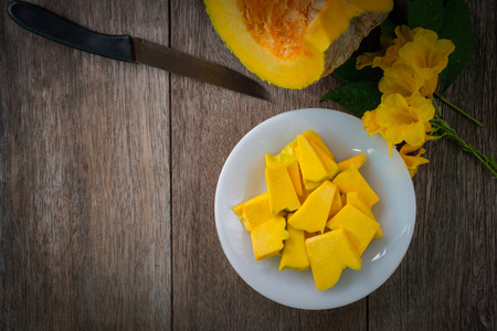 sliced pumpkin on white plate, beside knife on old wood table, is a cultivar of a squash plant that be used for food and recreation for instant, pie, Thanksgiving meals, Halloween decoration