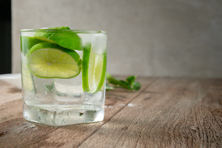 closed up glass of iced lime juice on wood table, infused with sliced lime, souce of Vitamin C Stock Photo