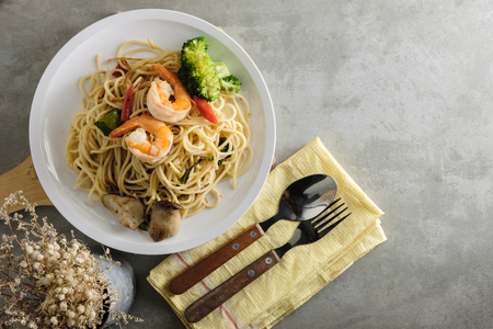 top view of spaghetti on table, spicy stir fried spaghetti with prawn, mushroom and broccoli beside the forks