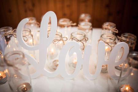 The word LOVE on white cloth around burning candles. Handmade. Scenery Stock Photo