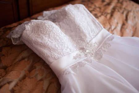 White lace wedding dress on the bed. Day