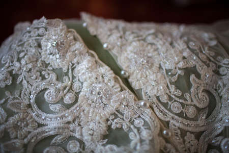 needle laces: white lace handmade wedding dress Stock Photo