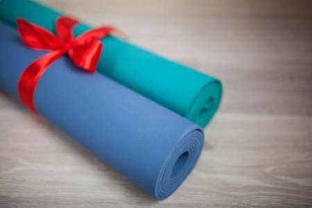 Two colored yoga Mat with a gift ribbon Stock Photo - 92016026