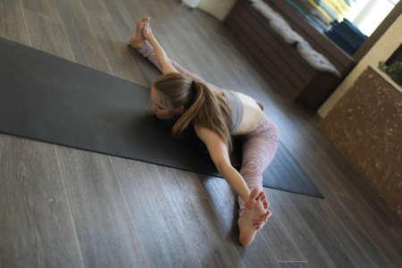 A young woman practicing Ashtanga yoga. Stockfoto