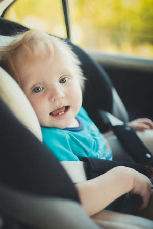 The child is sitting in a child seat in the car.