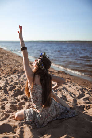 Young healthy woman practicing yoga on the beach at sunrise. Stockfoto