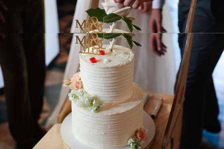 Multi-tiered white wedding cake with figures of the bride and groom. Close up
