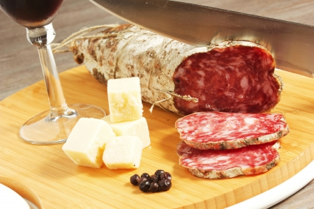 salami and cheese on a wood table photo