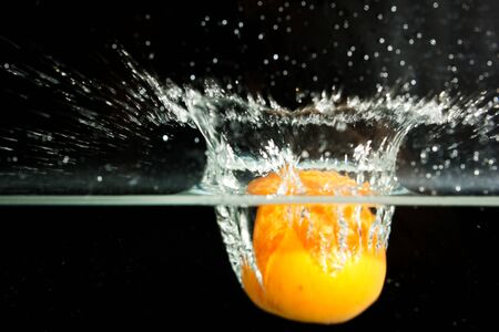 submerge: apricot in the water on a black background
