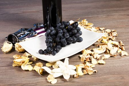 bottle of wine red with grapes and corkscrew on the table photo