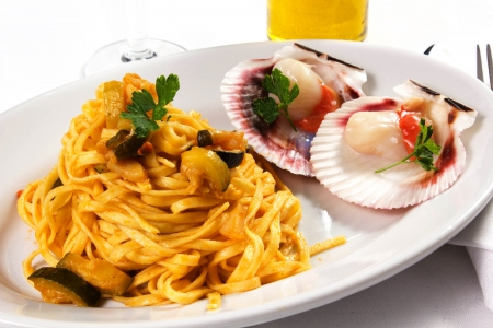 pasta with scallops and zucchini on the table  photo