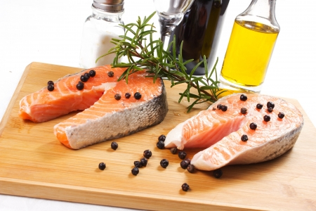 slices of salmon on platter with rosemary, pepper and oil photo