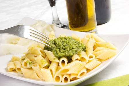 Pasta with pesto sauce, fresh basil and cheese on white plate photo