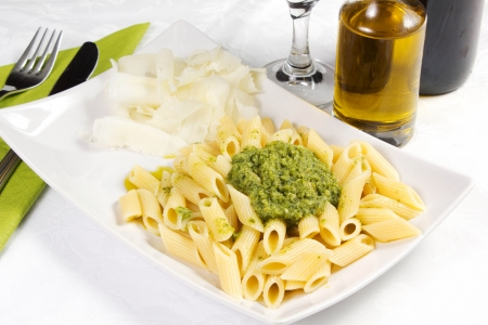 Pasta with pesto sauce, fresh basil and cheese on white plate Stock Photo