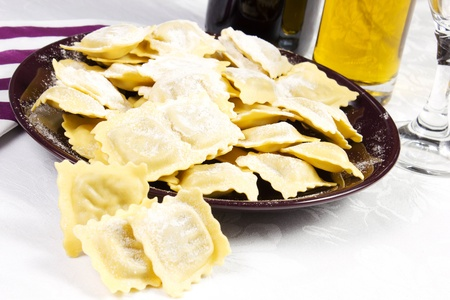 ravioli in the dish on a white background with oil and utensil photo