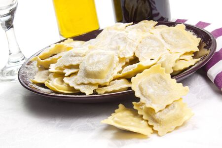 ravioli in the dish on a white background with oil and utensil