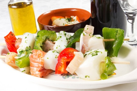 foodfish skewers  on a white table with oil and wine photo