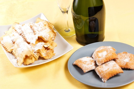 yellows: carneval cakes on the table, chiacchere, bugie, champagne and glass