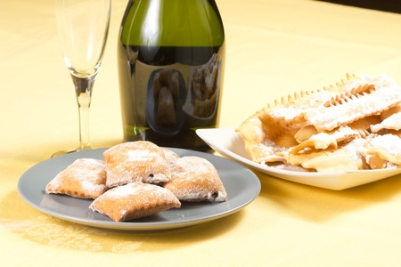 carneval cakes on the table, chiacchere, bugie, champagne and glass photo