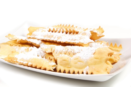 carneval cakes on a white background, chiacchere, bugie, champagne and glass photo