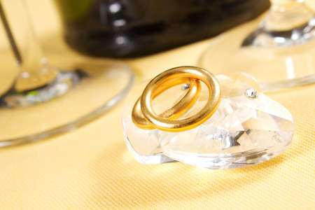wedding rings on crystal heart on the table with champagne photo